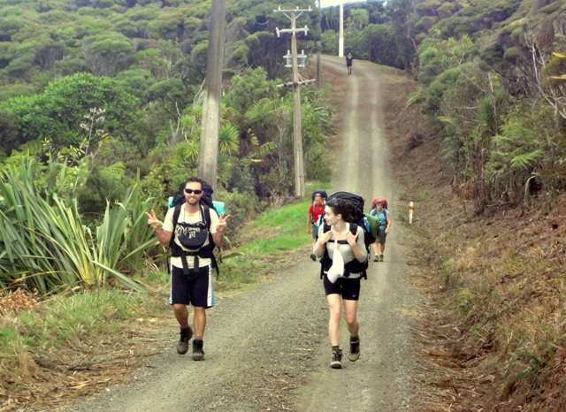 Two couples coming along Log Race Road, see the lone walker back at the far power pole
